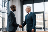 Photo cheerful businessman shaking hands with african american diplomat