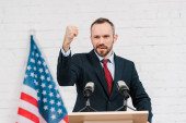 Photo selective focus of emotional speaker with clenched fist talking near microphones and american flag