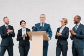 multicultural businessmen and businesswomen applauding to bearded speaker