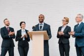 happy businessmen and businesswomen applauding to african american speaker