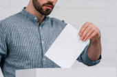 cropped view of voter putting blank ballot in voting box