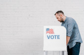 Photo side view of bearded citizen voting near stand with vote lettering and flag of america