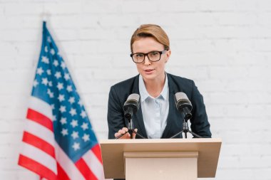 Attractive speaker in glasses talking near microphones and american flag stock vector