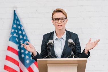 Beautiful speaker in glasses gesturing while talking near microphones stock vector