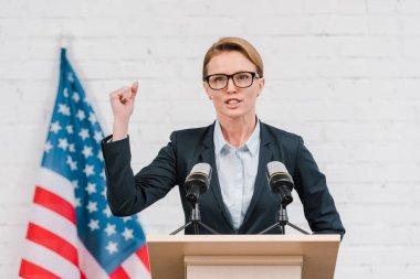 Emotional speaker in glasses gesturing while talking near microphones stock vector