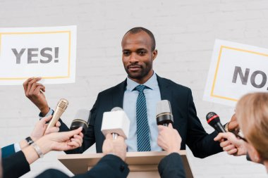 cropped view of journalists with microphones near african american diplomat holding placards with yes and no lettering
