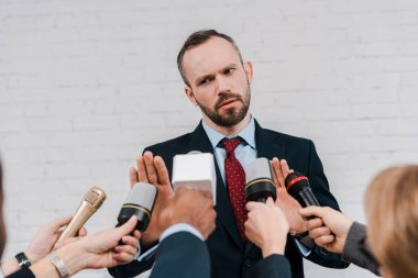 cropped view of journalists holding microphones near bearded diplomat showing no gesture