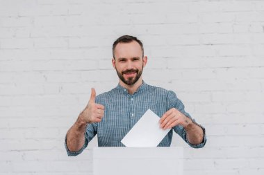 cheerful voter showing thumb up while holding blank ballot