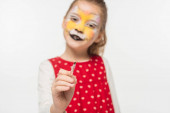 selective focus of adorable kid with tiger muzzle painting on face pointing with paintbrush at camera isolated on white
