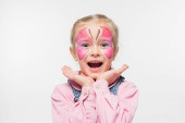 excited child with butterfly painting on face holding hands near face while looking at camera isolated on white