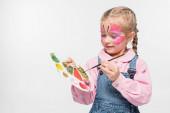 rozkošné dítě s motýlí malbou na obličeji drží paletu a štětec izolované na bílém