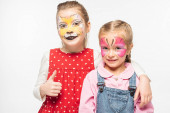 adorable kid with cat muzzle painting on face showing thumb up while embracing friend with painted butterfly mask isolated on white