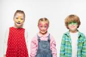 usmívající se přátelé s barevnými obrazy obličeje při pohledu na kameru izolované na bílém