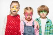 nespokojení přátelé s barevnými malbami obličeje při pohledu na kameru izolované na bílém