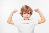 rozkošný chlapec s maskou superhrdiny namalovanou na tváři demonstrující sílu izolované na bílém