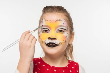 Cute kid with tiger muzzle painted on face painting on eyebrow with paintbrush isolated on white stock vector