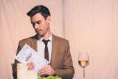 jóképű, elegáns férfi olvasás menü, miközben ül az étteremben
