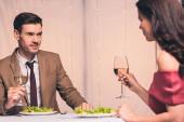 šťastný, elegantní muž a žena sedí u servírovaného stolu a drží sklenici bílého vína