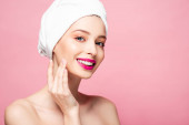 usmívající se nahá žena v bílém ručníku dotýkající se tváře izolované na růžové