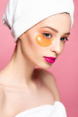beautiful woman in eye patch and white towel isolated on pink