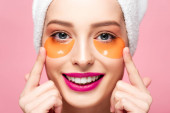 smiling girl touching face with eye patches isolated on pink