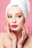 mladá nahá žena v hydratační obličejové masky při pohledu pryč izolované na růžové