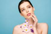 nahá mladá žena s květinami na krku dotek tvář izolované na modré