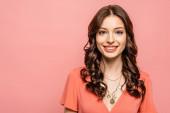 šťastná mladá žena usmívá na kameru izolované na růžové