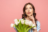 Photo dreamy girl looking away while holding bouquet of white tulips and touching cheek isolated on pink