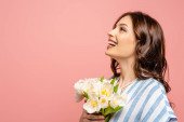 happy girl looking up while holding bouquet of white tulips isolated on pink