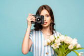 attractive young woman taking photo on digital camera while holding bouquet of white tulips isolated on blue