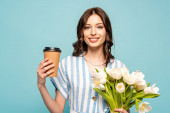 Fotografie happy young woman holding coffee to go and bouquet of white tulips isolated on blue