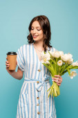 happy young woman holding coffee to go and bouquet of white tulips isolated on blue