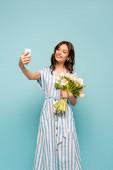 vonzó fiatal nő csinál szelfi okostelefon, miközben gazdaság fehér tulipán elszigetelt kék