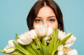 beautiful young woman enjoying flavor of white tulips while looking at camera isolated on blue