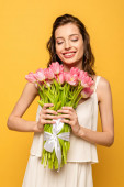 happy young woman holding bouquet of pink tulips while smiling with closed eyes isolated on yellow