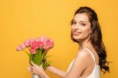 krásná mladá žena usmívá na kameru, zatímco drží kytice růžových tulipánů izolovaných na žluté