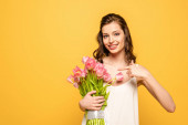 smiling young woman pointing with finger at bouquet of pink tulips while looking at camera isolated on yellow