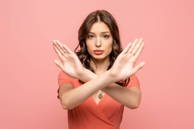 serious young woman showing stop gesture while looking at camera isolated on pink
