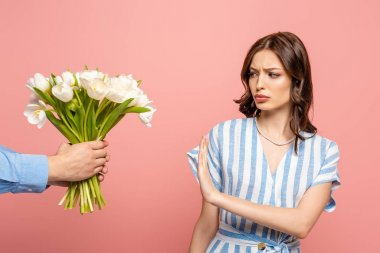 Partial view of man presenting bouquet of white tulips to displeased girl showing no gesture isolated on pink stock vector