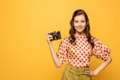 vidám fiatal nő kezében digitális fényképezőgép, miközben álló kézzel csípő elszigetelt sárga