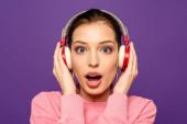 šokované dívka při pohledu na kameru při dotyku bezdrátových sluchátek izolovaných na fialové