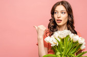 surprised young woman looking away and pointing with thumb while holding white tulips isolated on pink