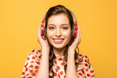 Happy young woman touching headphones while smiling at camera isolated on yellow stock vector
