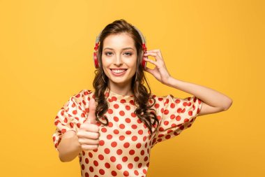 Cheerful young woman in wireless headphones showing thumb up while smiling at camera isolated on yellow stock vector