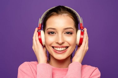 Happy girl smiling at camera while touching wireless headphones isolated on purple stock vector