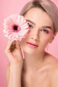 něžná nahá žena s růžovým make-upem drží gerbera květiny, izolované na růžové