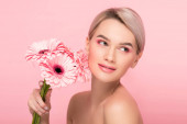 Fotografie beautiful girl holding pink gerbera flowers, isolated on pink