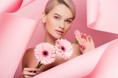 Attractive girl with pink flowers and makeup in torn paper, on pink stock vector