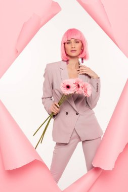 Attractive stylish girl in suit and pink wig holding flowers and posing in torn paper,  isolated on white stock vector